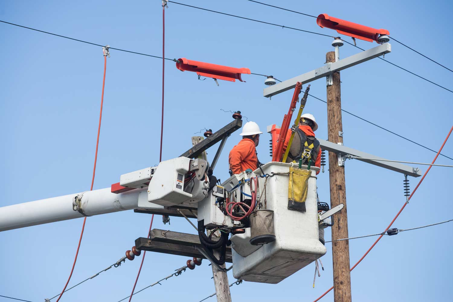 Linemen in bucket truck working on electric utility lines